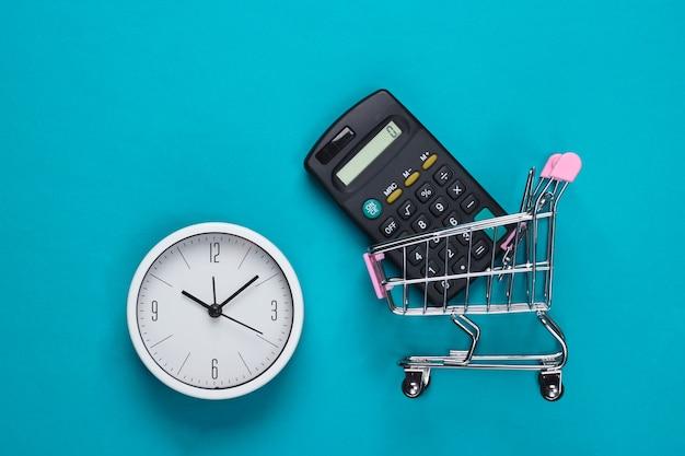 Einkaufszeit. supermarktwagen mit taschenrechner, uhr auf blauer oberfläche. minimalismus. draufsicht