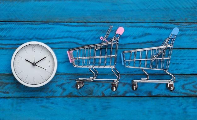 Einkaufszeit. supermarktwagen mit uhr auf blauer holzoberfläche. minimalismus. draufsicht