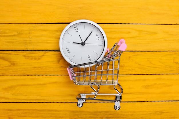 Einkaufszeit. supermarktwagen mit uhr auf gelber holzoberfläche. minimalismus. draufsicht