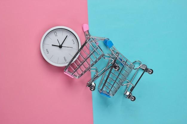 Einkaufszeit. supermarktwagen mit uhr auf rosa blauem hintergrund. minimalismus. draufsicht
