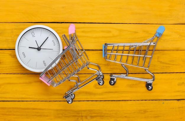 Einkaufszeit. supermarktwagen uhr auf gelber holzoberfläche. minimalismus. draufsicht