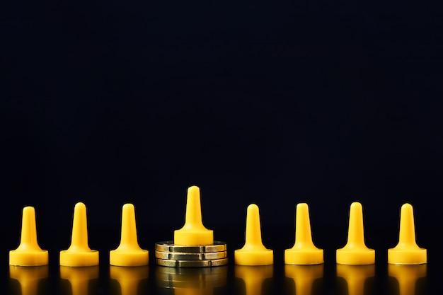 Einkommensunterschiede zwischen arm und reich konzept. brettspielfigur auf haufen münzen und menge aus den anderen figuren