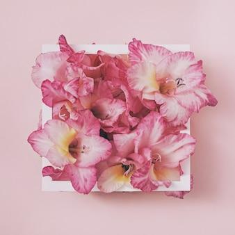 Einladung mit gladiolenblumen in einem rahmen. minimales trendiges konzept für hochzeitseinladung.