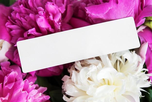 Einladungskarte und rosa pfingstrosenblumen