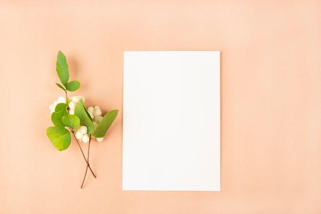 Einladungskartenmodell. vorlage leere grußkarte zur hochzeit, zum geburtstag und zu anderen ereignissen. papier auf pfirsichfarbhintergrund mit weißen blumen. konzept des romantischen schreibens zum valentinstag
