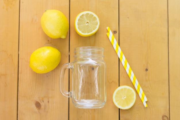 Einmachglas, frische zitronen und strohe auf holztisch. flach liegen. bereit für einen cocktail. sommerferien urlaub.