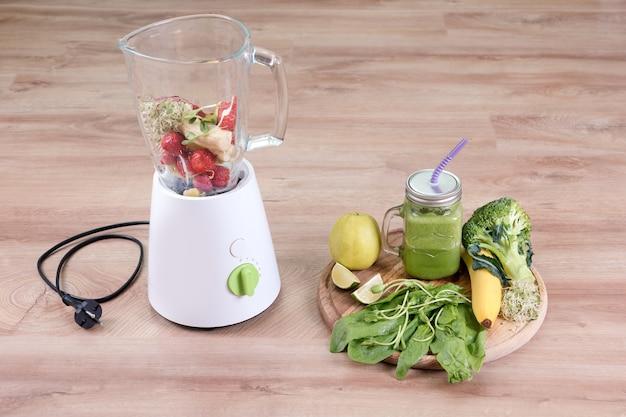 Einmachglas mit diätgetränk mit brokkoli, spinat, microgreens, limette und banane und mixer voll mit zutaten auf holzhintergrund