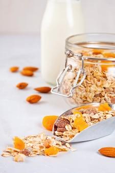 Einmachglas mit hausgemachtem müsli mit nüssen und trockenfrüchten sowie mandelmilch. gesunde ernährung frühstück