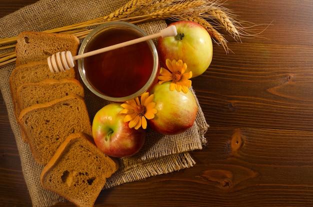 Einmachglas mit honig, roggenbrot, äpfeln, gelbem gänseblümchen und ohren