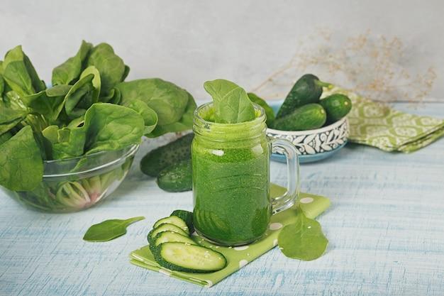 Einmachglasbecher gefüllt mit frischem grünem spinat und gurken-smoothie auf hellblauem holzhintergrund. gesundes essen und vegetarisches konzept.