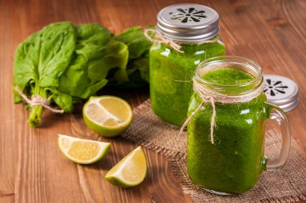 Einmachglasbecher gefüllt mit grünem spinat und grünkohlgesundheits-smoothie