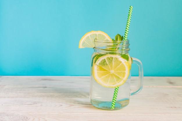 Einmachglasglas selbst gemachte limonade mit zitronen, minze und papierstroh auf türkishintergrund. erfrischendes sommergetränk.