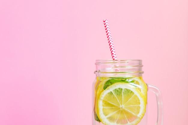 Einmachglasglas selbst gemachte limonade mit zitronen, minze und rotem papierstroh auf rosa hintergrund. erfrischendes sommergetränk.