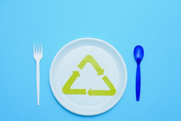 Einmalgebrauch, einweggeschirr und recyclingschild auf hintergrund. löffel, gabeln