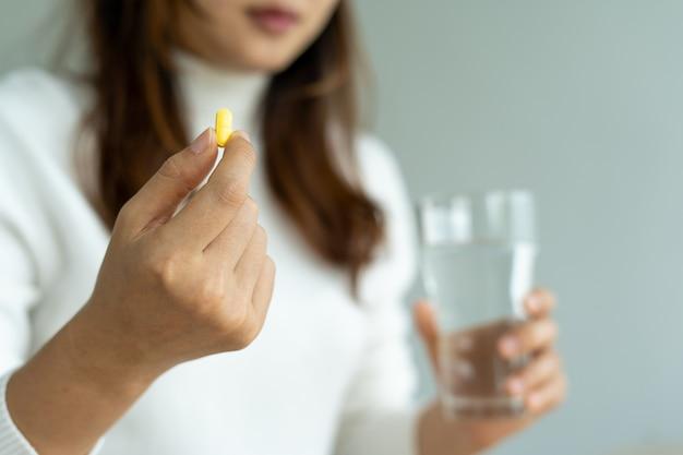 Einnahme von medizinpillen-konzept. frau hält in den händen die medizinpillen und ein glas wasser. gesundheitsversorgung oder behandlung von virusinfektionen