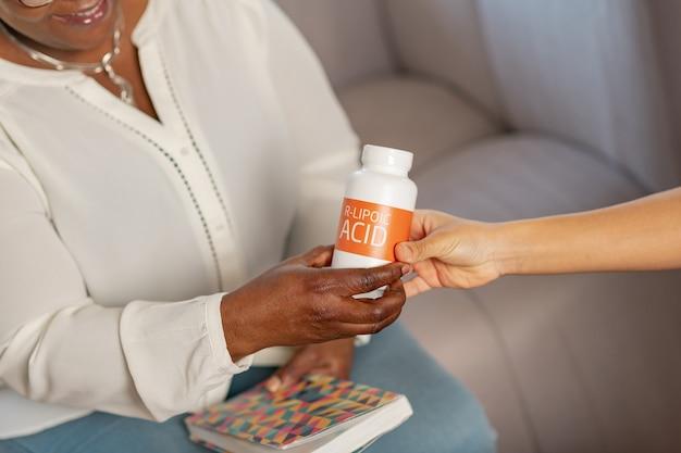 Einnahme von nahrungsergänzungsmitteln. nahaufnahme eines lächelnden gealterten patienten des pflegeheims, der nahrungsergänzungsmittel von der krankenschwester nimmt