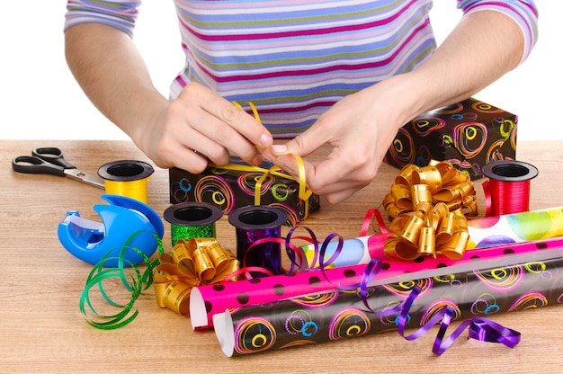 Einpacken von geschenken umgeben von papier, bändern und schleifen