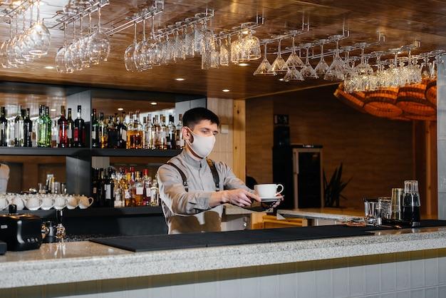 Einreichung eines barista in einer maske aus köstlichem bio-kaffee im modernen café während der pandemie