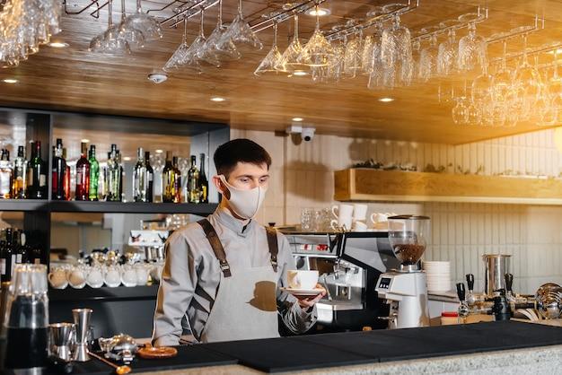 Einreichung eines barista in einer maske aus köstlichem bio-kaffee in einem modernen café während der pandemie