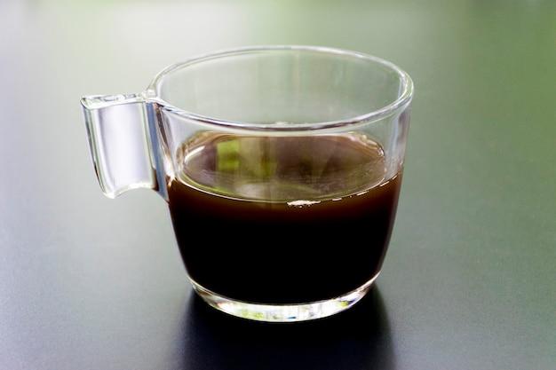 Eins des schwarzen kaffees auf schwarzem schreibtisch reflexionslicht der grünen natur