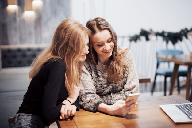 Eins-zu-eins-sitzung zwei junge geschäftsfrauen, die bei tisch im café sitzen mädchen zeigt ihr freundbild auf schirm von smartphone. auf dem tisch ist notebook geschlossen. freunde treffen