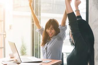 Eins-zu-Eins-Treffen. Zwei junge Geschäftsfrauen, die am Tisch im Café sitzen. Mädchen zeigt Kollegeninformationen über Laptopbildschirm. Mädchen, welches den Smartphone Blogging verwendet. Teamwork-Geschäftstreffen. Freiberufler arbeiten.