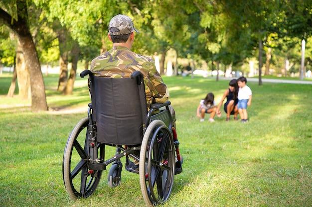 Einsam behinderter pensionierter soldat im rollstuhl, der seine frau und seine kleinen kinder betrachtet, die zusammen im park spielen. rückansicht. kriegsveteran oder behindertenkonzept