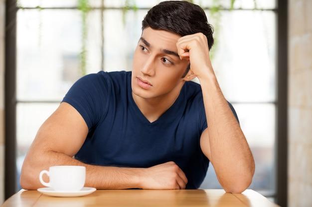 Einsam fühlen. frustrierter junger mann, der im restaurant sitzt und den kopf in der hand hält