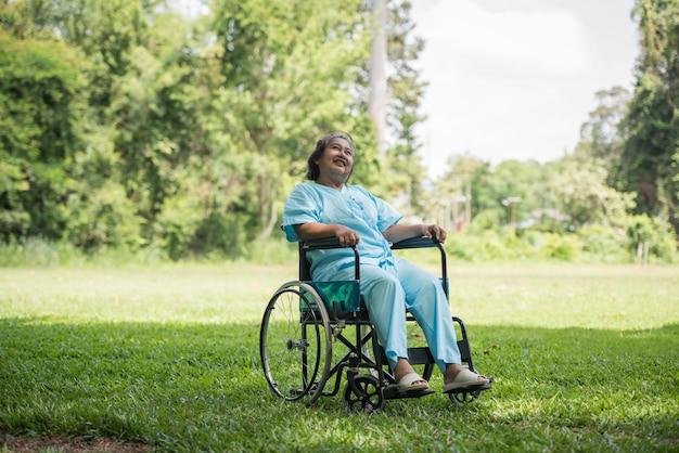 Einsame ältere frau, die auf rollstuhl am garten im krankenhaus sitzt