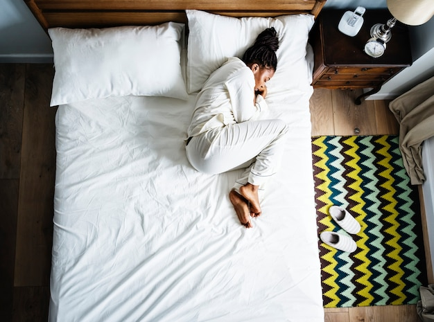 Einsame afroamerikanerfrau auf bett alleine schlafend