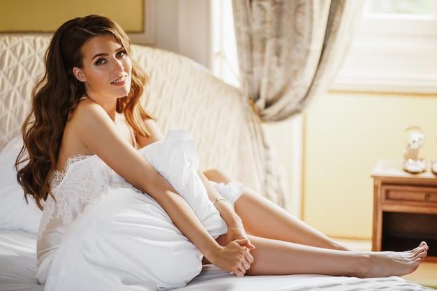 Einsame braut sitzt auf dem bett in einem großen hotelzimmer