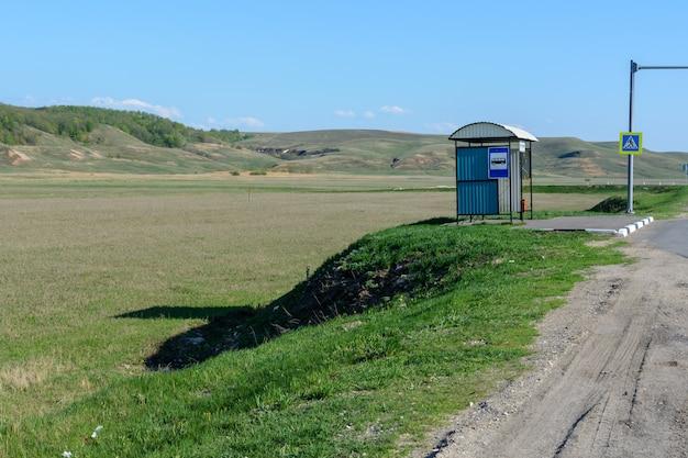 Einsame bushaltestelle vor dem hintergrund einer wunderschönen frühlingslandschaft, felder, wiesen, wälder und hügel. busverbindung auf dem land. warmer sonniger tag.