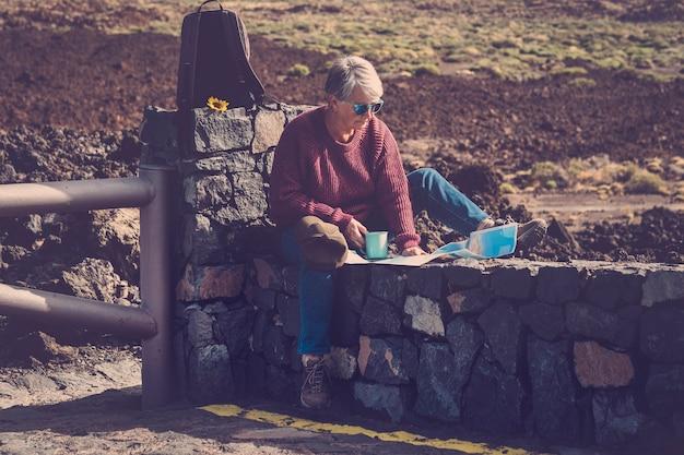 Einsame erwachsene ältere trekker-forscherin während einer pause über den bergen, die einen tee oder kaffee trinkt
