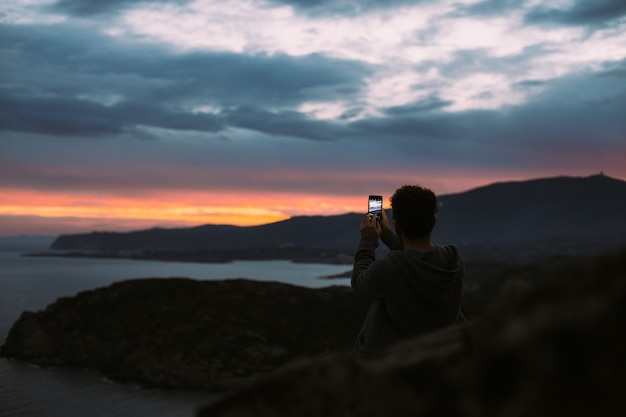 Einsame figur eines touristen oder reisenden, die auf einer klippe oder einem berg steht