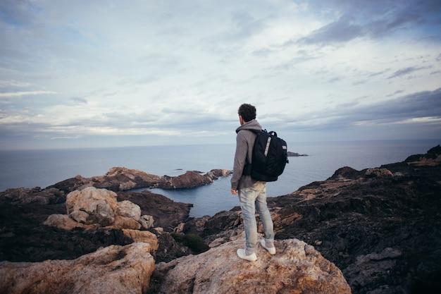 Einsame figur oder abenteurer und entdecker mit großem rucksack für drohnen