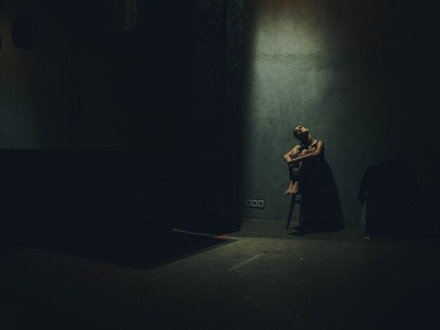 Einsame frau, die auf einem stuhl sitzt, der beine in einem dunklen raum umarmt und silhouette fällt