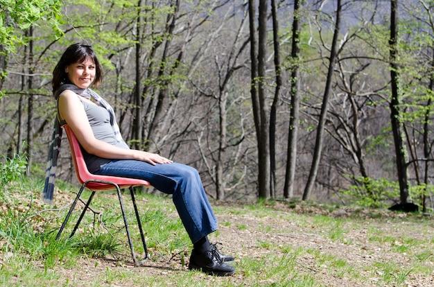 Einsame frau, die auf einem stuhl sitzt und sich in einem park entspannt