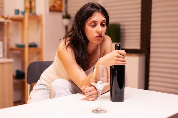 Einsame frau mit einer flasche rotwein