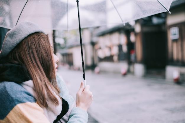 Einsame frau mit regenschirm wartet auf den regen auf der straße in japan.