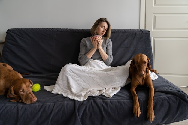 Einsame frau verbringt das wochenende zu hause und trinkt tee mit zwei hunden ohne freund und freunde nach der scheidung