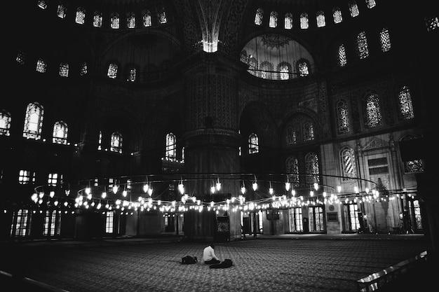 Einsame gläubige innerhalb der blauen moschee, die betet.