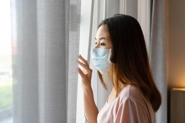 Einsame junge asiatische frau in der zuckerhaltigen gesichtsmaske bleiben zu hause für selbstquarantäne isoliert.