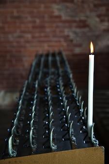 Einsame kerze in einer italienischen abtei. konzept der hoffnung, des glaubens, der einsamkeit