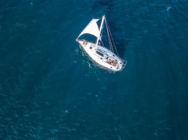 Einsame lokalisierte yacht unter dem segel mit dem hohen mast, der in draufsicht der ruhigen seeantenne geht