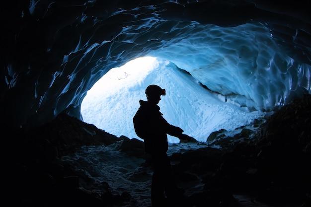 Einsame männliche wanderung in den bergen in einem käfig, der tagsüber mit schnee bedeckt ist