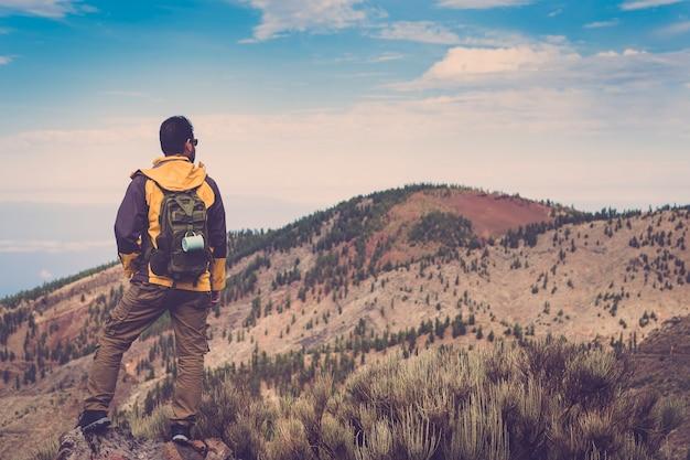 Einsame mann abenteuerzeit und trekking, wandern in den bergen und genießen den alternativen urlaubslebensstil allein mit der natur. berge von teneriffa und blauer himmel vor einem männchen. menschen in fernweh