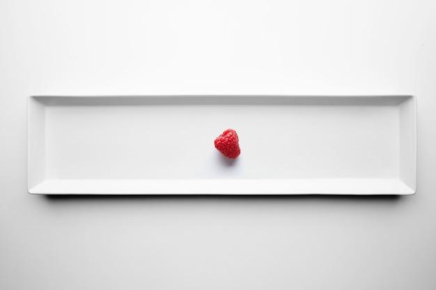 Einsame respberry isoliert auf weißem teller