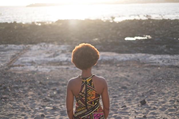 Einsame schöne schwarze rasse mädchen afrikanische ethnische von hinten betrachtet mit blick auf den sonnenuntergang und das licht über dem meer im urlaub. reisekonzept für junge leute im fernweh. retro '70 jahre haare