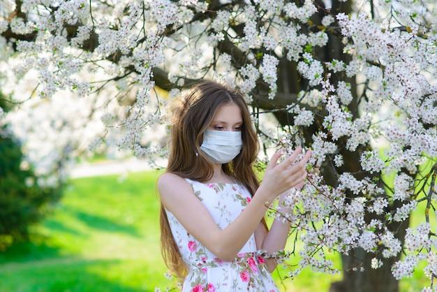 Einsame teenager-mädchen, die schutzmedizinmaske gegen virus und allergie trägt, die frühlingsblumenblüte im blühenden garten genießt