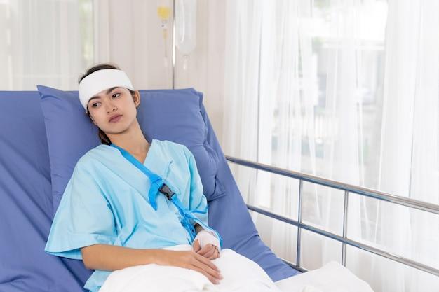 Einsame unfallpatienten verletzungsfrau auf bettpatienten im krankenhaus wollen nach hause gehen - medizinisches konzept